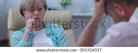 Concerned therapist is listening to her patient's problems - stock photo