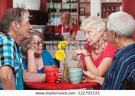 Concerned woman conversing with friends in bistro - stock photo
