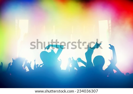 Concert, disco party. People with hands up having fun in night club lights - stock photo
