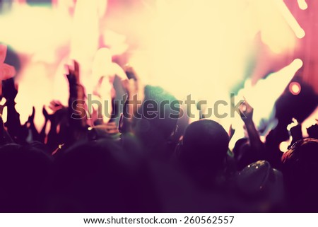 Concert, disco party. People with hands up having fun in night club lights. Vintage mood - stock photo