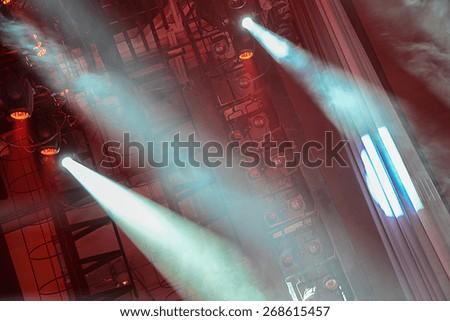 Concert spotlights shining red light and fog - stock photo