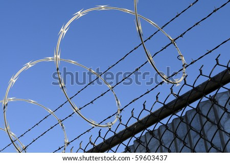 Concertina razor wire and barbed wire atop a security fence - stock photo
