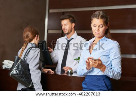 Concierge at hotel reception serving guests with woman checking her smartphone - stock photo