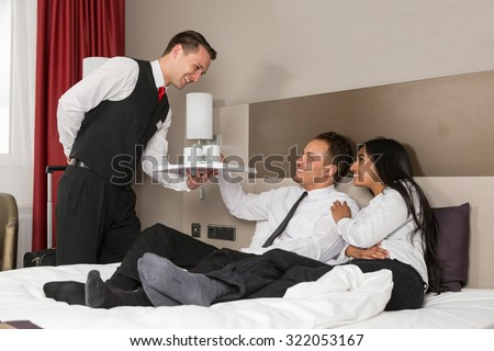 Concierge serving coffee to guests in hotel room - stock photo
