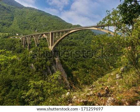 concrete arch bridge over the river Tara in northern Montenegro - stock photo