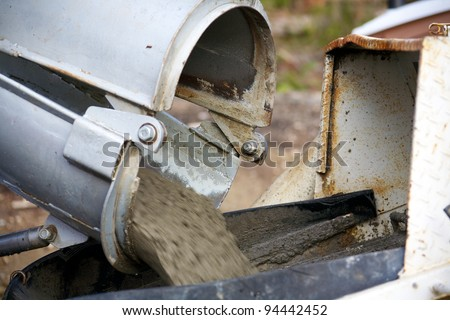 Concrete being poured from a truck into a concrete pump at a construction site - stock photo