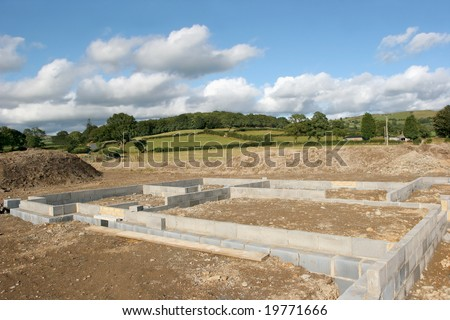 Concrete  block foundations for a new building on a construction site in rural countryside. - stock photo