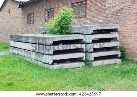 Concrete blocks near the brick building - stock photo