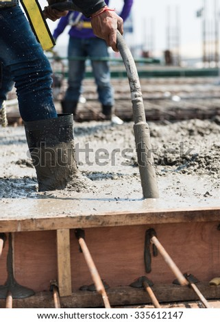 concrete casting work. using concrete vibrator for compacting concrete of stiff consistency.  selection focus to vibration machine. - stock photo