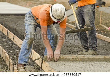 Concrete construction contractor installing a sidewalk, curb and storm drainage gutter on a new urban road street project - stock photo