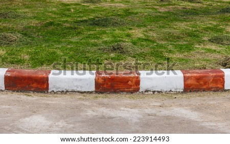 Concrete curb on the green grass.Edge of pavement to the lawn - stock photo
