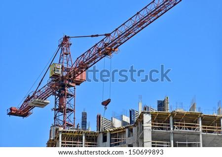 Concrete formwork and crane on construction site - stock photo