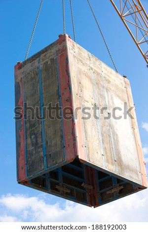 Concrete formwork lifting during hoisting construction works with tower crane - stock photo