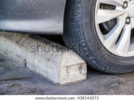 Concrete grey parking stoppers with auto tire in parking lot. - stock photo