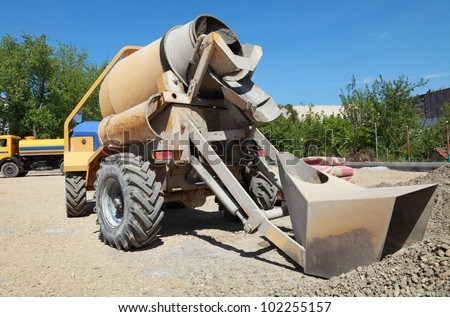 Concrete mixer at road construction site with heap of gravel - stock photo