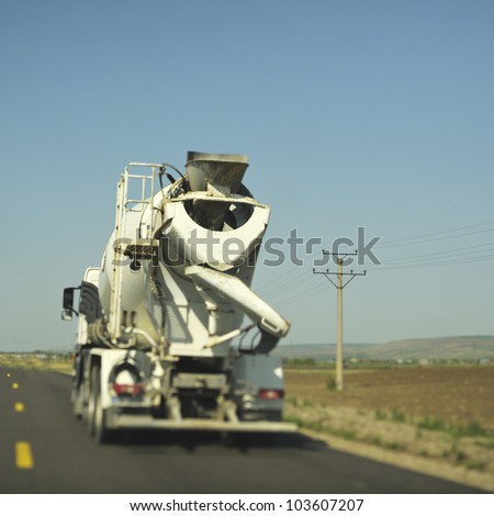Concrete mixer (cement) truck driving on the freeway. Real tilt-shift lens used to get the special blur effect. Useful file for your construction article, company brochure and other media needs. - stock photo