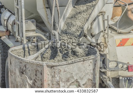 Concrete mixer truck pouring liquid concrete into the tower crane bucket at the construction site.Close-up image - stock photo