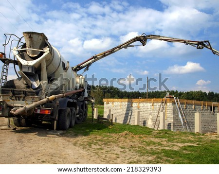 concrete mixer truck with pump on the site is preparing to pour concrete on the roof of a small house - stock photo