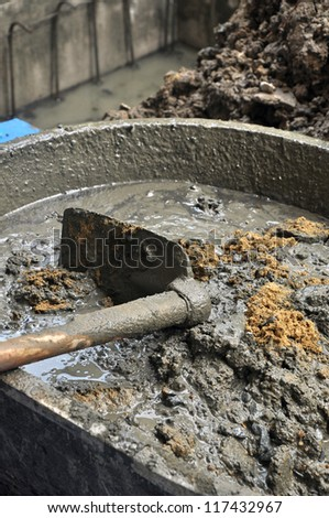 concrete mixing with a shovel in construction site - stock photo