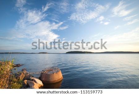 Concrete mooring bollard with ships chain on the coast of Saimaa lake in Finland - stock photo