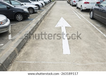 Concrete National Road with White Arrow Sign with Various Private Cars Parking on the Sides - stock photo