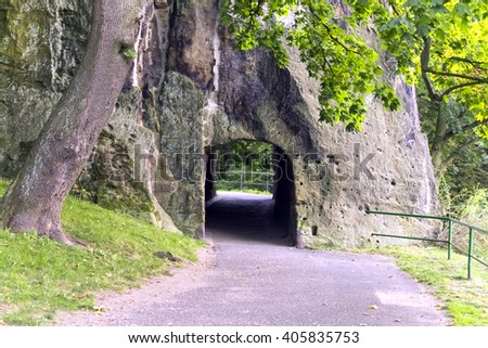 Concrete path with a fence disappearing into the old stone arch in the green of the trees in the park - stock photo