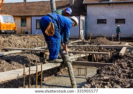 Concrete pouring. Construction workers are pouring concrete in building foundation, directing the pump tube on right direction. - stock photo