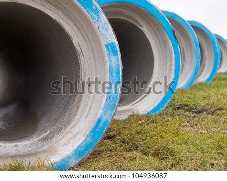 Concrete sewage construction pipes on a building site - stock photo