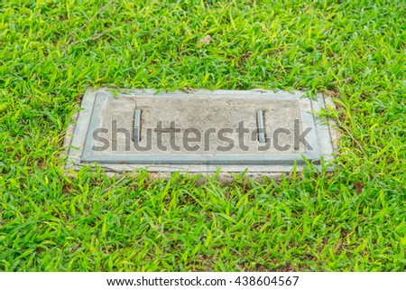 concrete sewer cover in the garden, cement sewer cover on the grass field. - stock photo