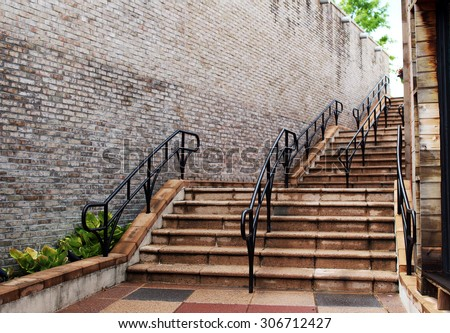 Concrete steps with black metal railings after rain (view from the base of the stairs)  - stock photo
