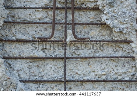 concrete wall with rusty reinforcement rods background - stock photo