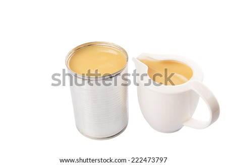 Condensed milk in tin can and white ceramic milk pitcher over white background - stock photo