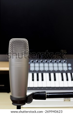 condenser microphone , music synthesizer keyboard & black monitor in recording studio / copy space on top for music concept - stock photo