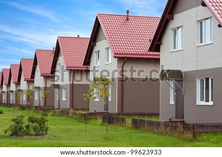 Condo for sale arranged in a row. Undeveloped gardens. - stock photo