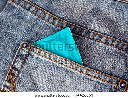 Condom in a jeans pocket - stock photo