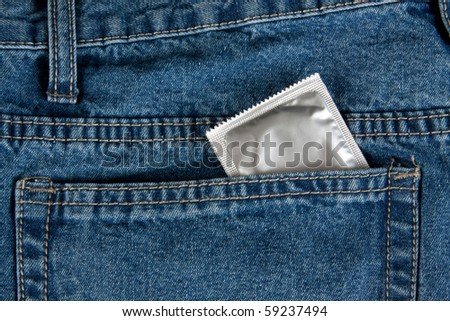 Condom in the pocket of a blue jeans - stock photo