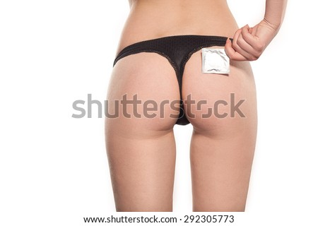 Condom near sexual ass of young beautiful woman, black thong, beautiful lingerie , safe sex - stock photo