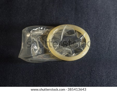 condom on a black background - stock photo