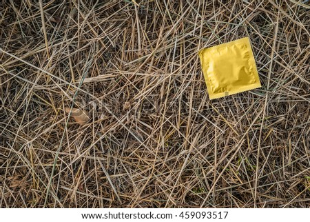 Condom surface. Gold condom lying in the manger - stock photo