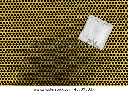 Condom surface. Silver condom lying on gold metal - stock photo