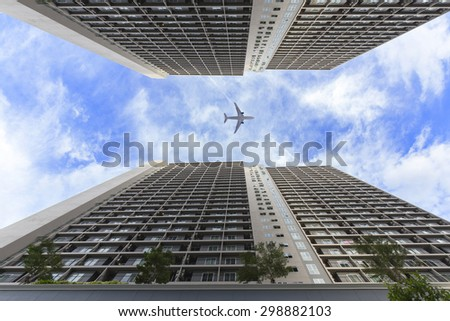 Condominiums and office buildings, airplanes on sky - stock photo