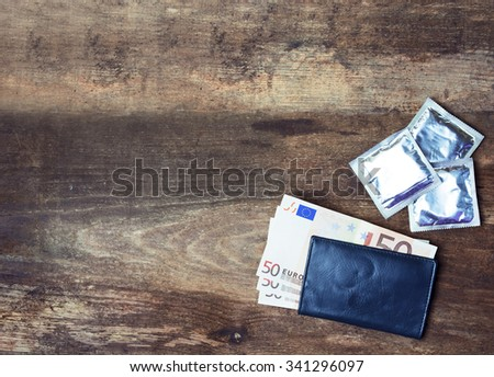 condoms and  Check folder with euro  on wooden background. space for text. dating, sex sales,prostitution concept - stock photo