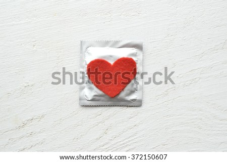condoms and red hearts  on white wooden background.love concept.Valentine's Day - stock photo