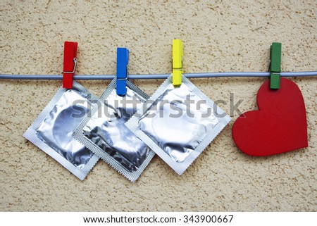 condoms and red love heart,  colorful wooden clothespin. space for text. valentine days, dating, making love concept - stock photo
