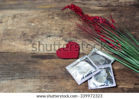 condoms and red love heart, flower  on wooden background. space for text. valentine days, dating, making love concept - stock photo