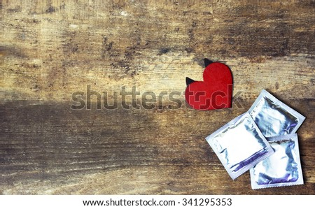 condoms and red love heart with horns on wooden background. space for text. valentine days, dating, making love concept - stock photo