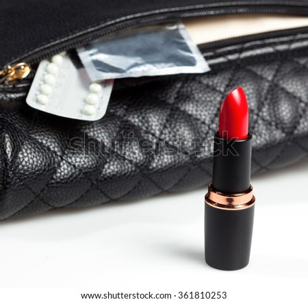 condoms, birth control pills and red lipstick, falling from woman's bag - stock photo