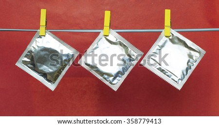condoms hanging on clothespins, valentines day background  selective focus image - stock photo