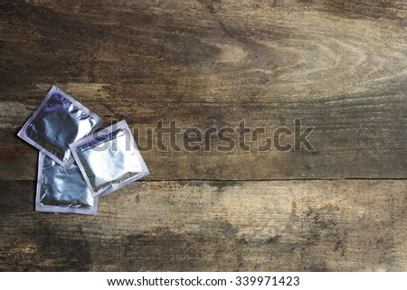 condoms on wooden background. space for text - stock photo