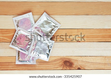 condoms on wooden background. toned image - stock photo
